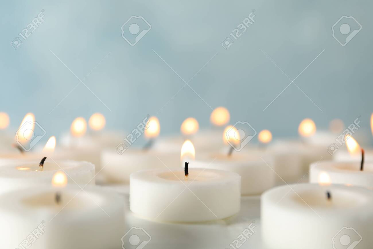 Group of burning candles against blue background, close up - 135268896