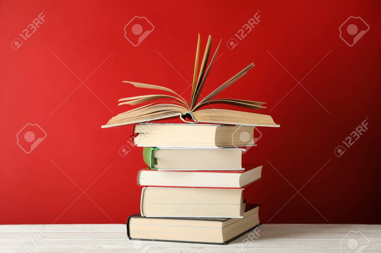 Stack of books against red background, space for text - 135633577