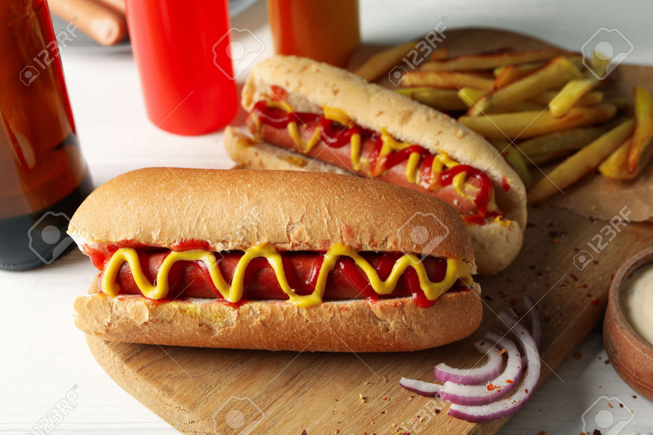 Tasty hot dogs, beer and sauces on white wooden background - 144371220