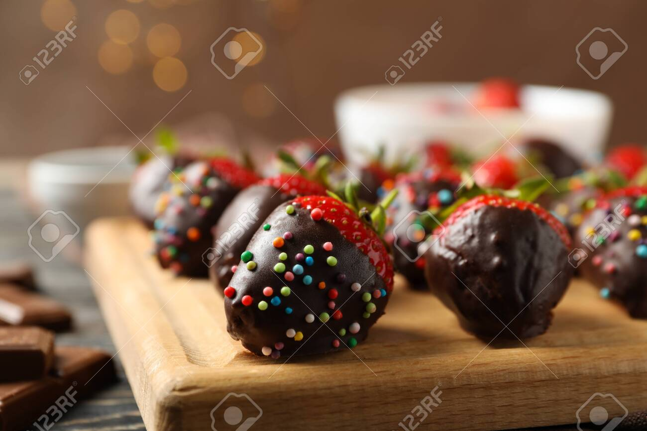 Chocolate fondue. Strawberry in chocolate on wooden background, close up - 148531068