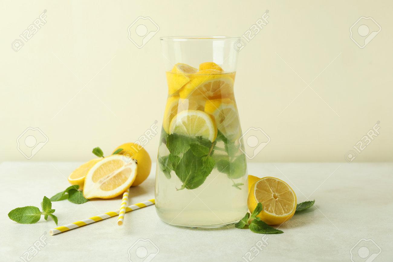 Jug of lemonade, lemons and straws on white textured table - 169087665