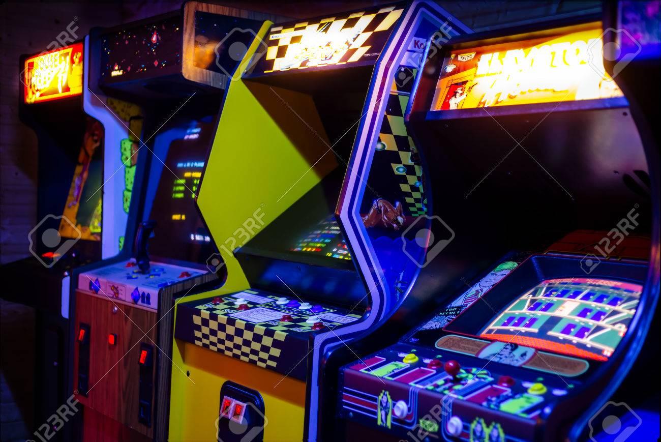 Fila De Viejos Videojuegos Arcade Con Pantallas Brillantes En Una