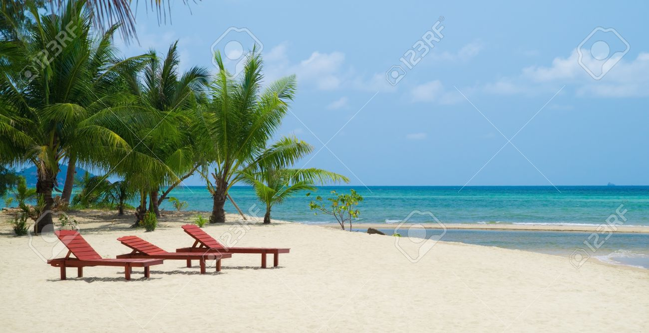 three red wooden beach chairs on white sand against blue ocean