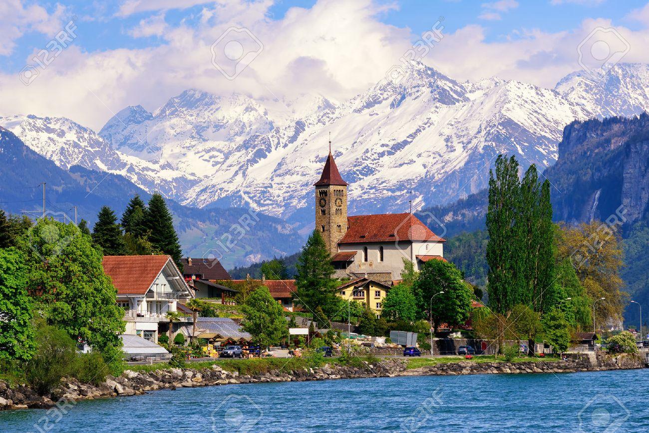 Brienz town on Lake Brienz by Interlaken, Switzerland, with snow covered Alps mountains in background - 59431011