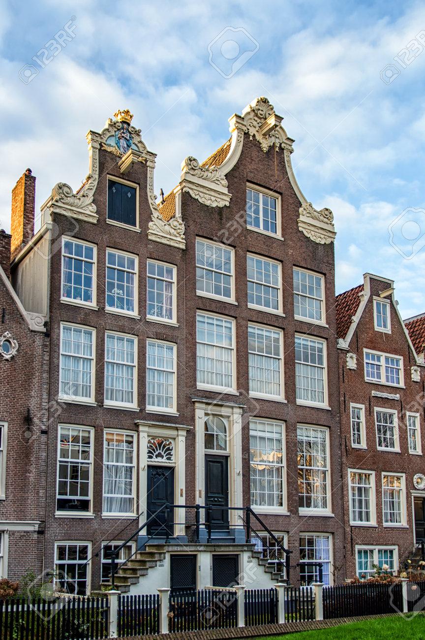Les façades d\'une rangée de belles maisons de canal Amsterdam dans la  lumière du matin contre un ciel bleu clair.