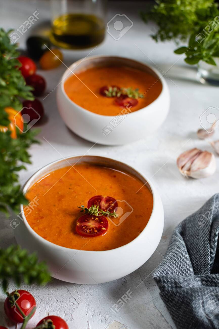 Traditional spanish tomato soup gazpacho in a bowl, flat lay on white concrete background - 130384311