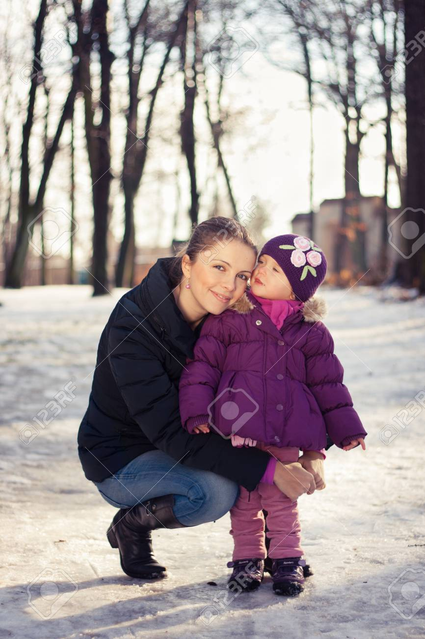Young mother and her baby girl outdoors on a snowy winter day Stock Photo - 16987185