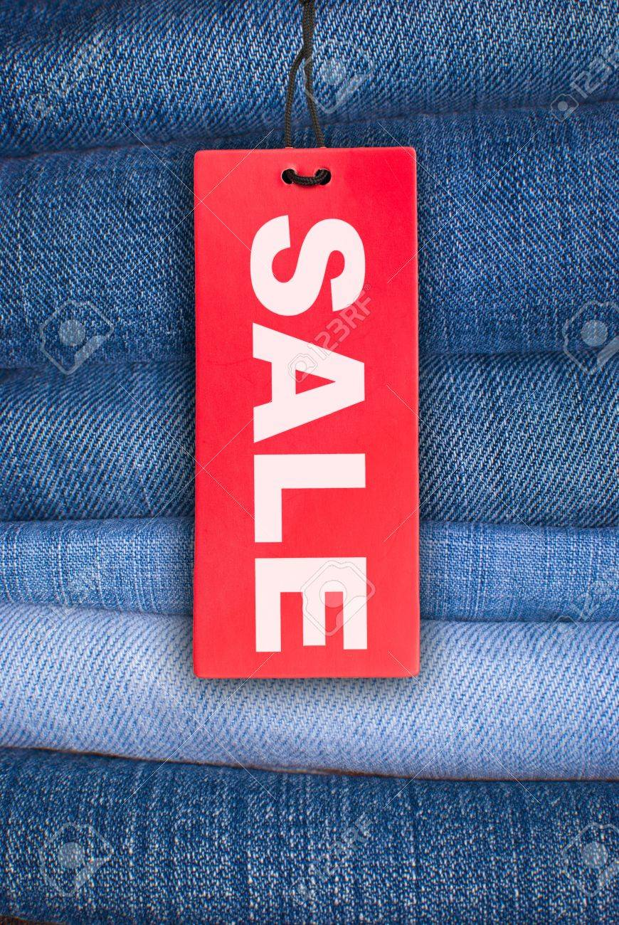 Red Sale Sign With Stack Of Blue Jeans In Background Stock Photo ...