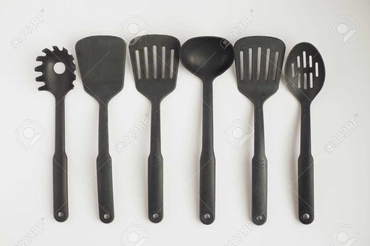 Black plastic kitchen cooking utensils shot overhead