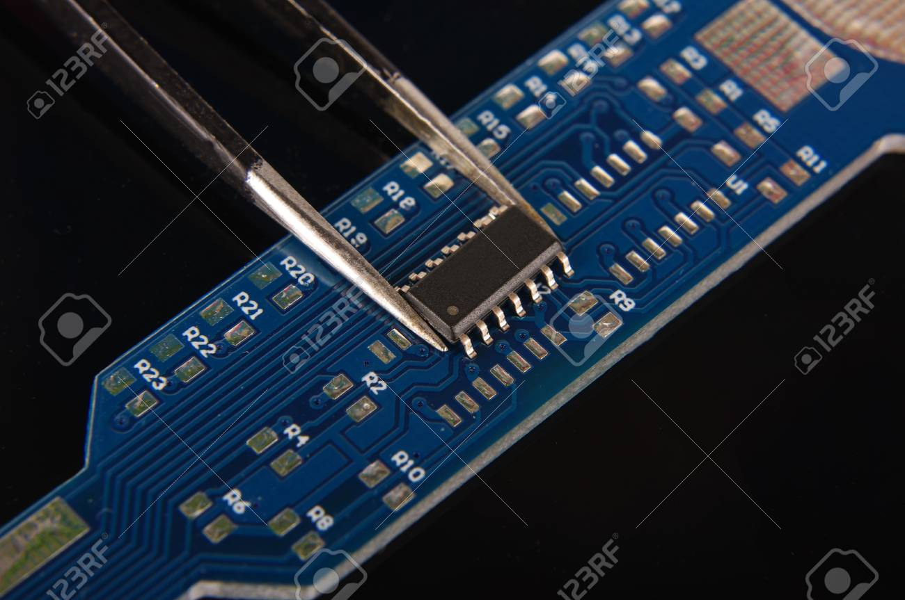 Small Electronics Integrated Circuit Ic On Empty Printed Board Ready For Hand Assembly Stock Photo