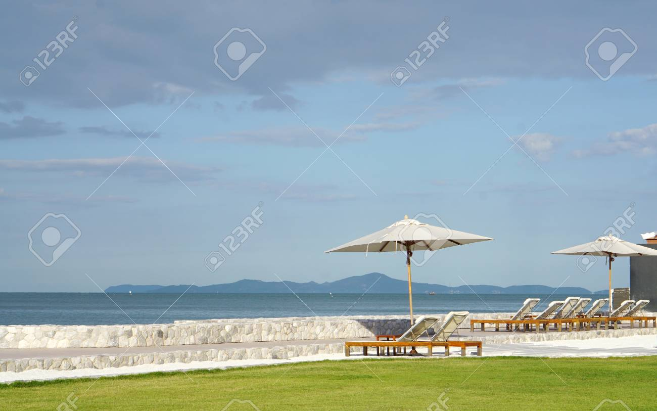 Stock Photo   White Color Recliner Beach Seating With White Parasol On White  Gravel And Green Lawn Facing The Sea Front In Thailand