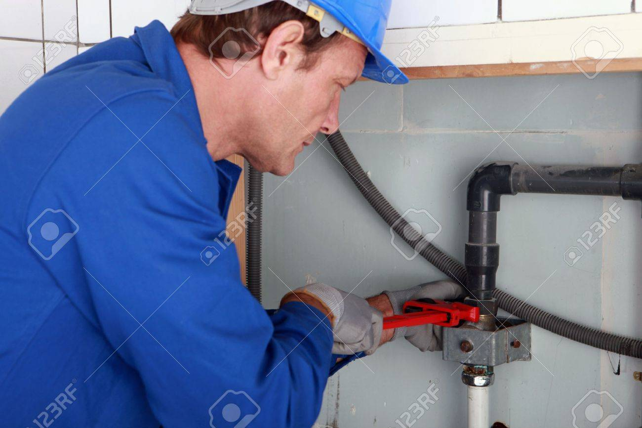 Plumber tightening a joint with a wrench Stock Photo - 10746772
