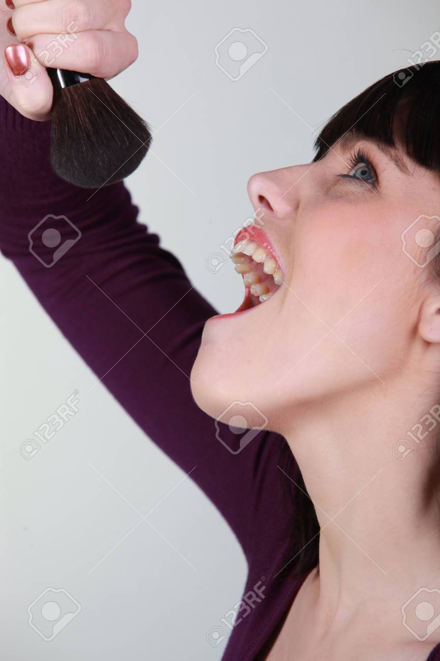 Woman singing into a blusher brush Stock Photo - 10746801