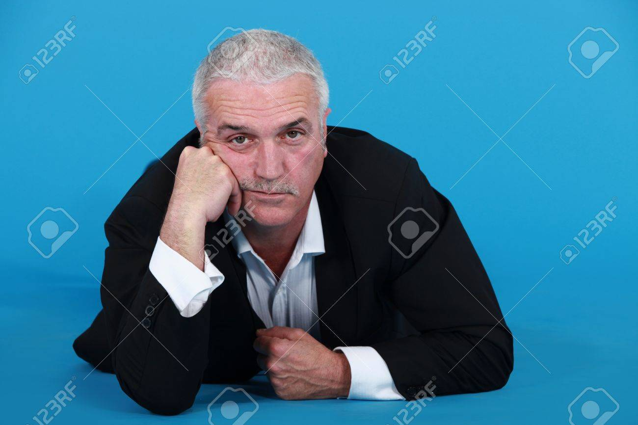 A mature bored businessman laying on the floor. Stock Photo - 10746207