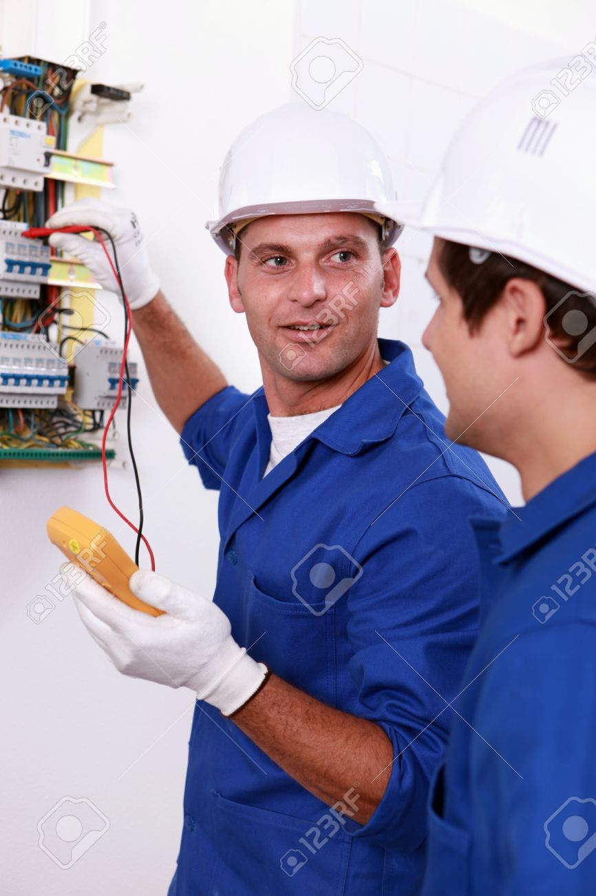 Two Electricians Testing Fuse Box Stock Photo Picture And Royalty Electrician