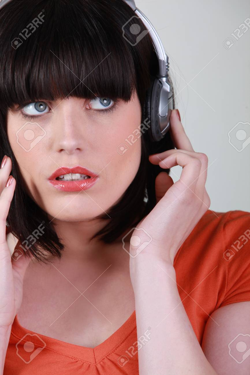 Attractive woman listening to music on headphones Stock Photo - 10783563