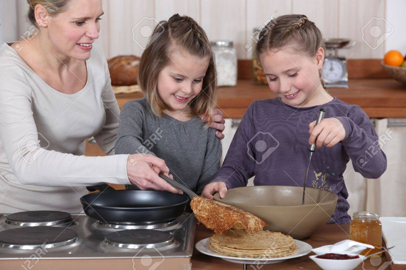 Woman cooking crepes with her daughters Stock Photo - 10854793