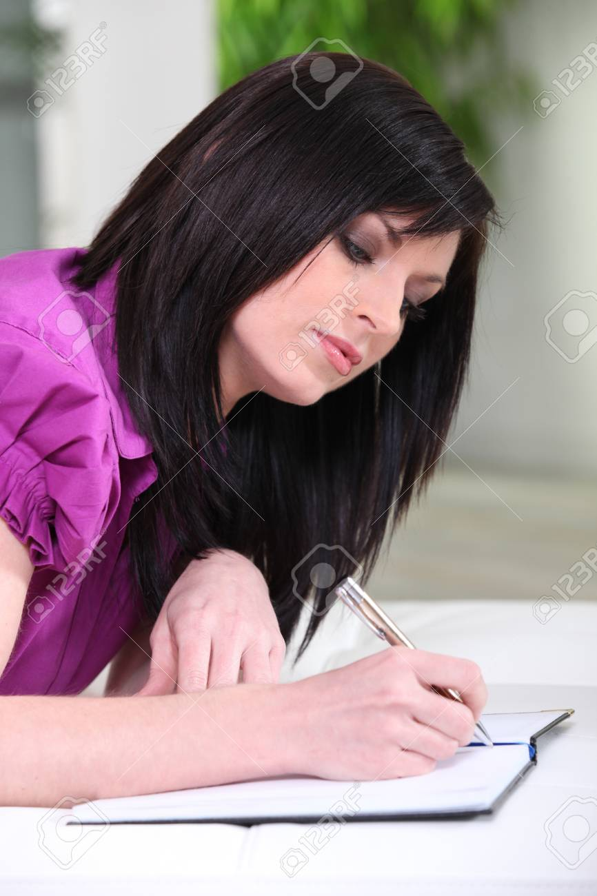 Young woman writing on a notebook Stock Photo - 10854492