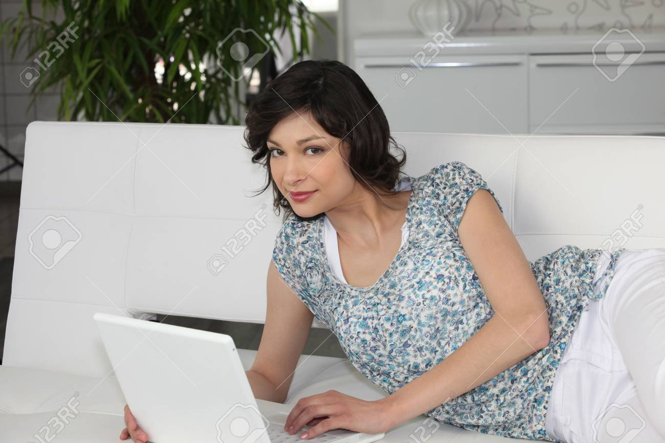 Woman laid in couch with laptop Stock Photo - 10855395