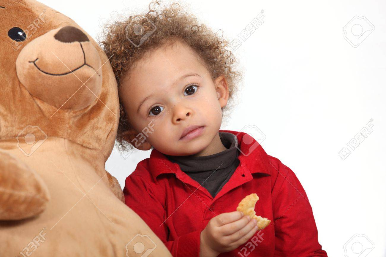 Toddler eating a cookie and playing with a toy Stock Photo - 11088111