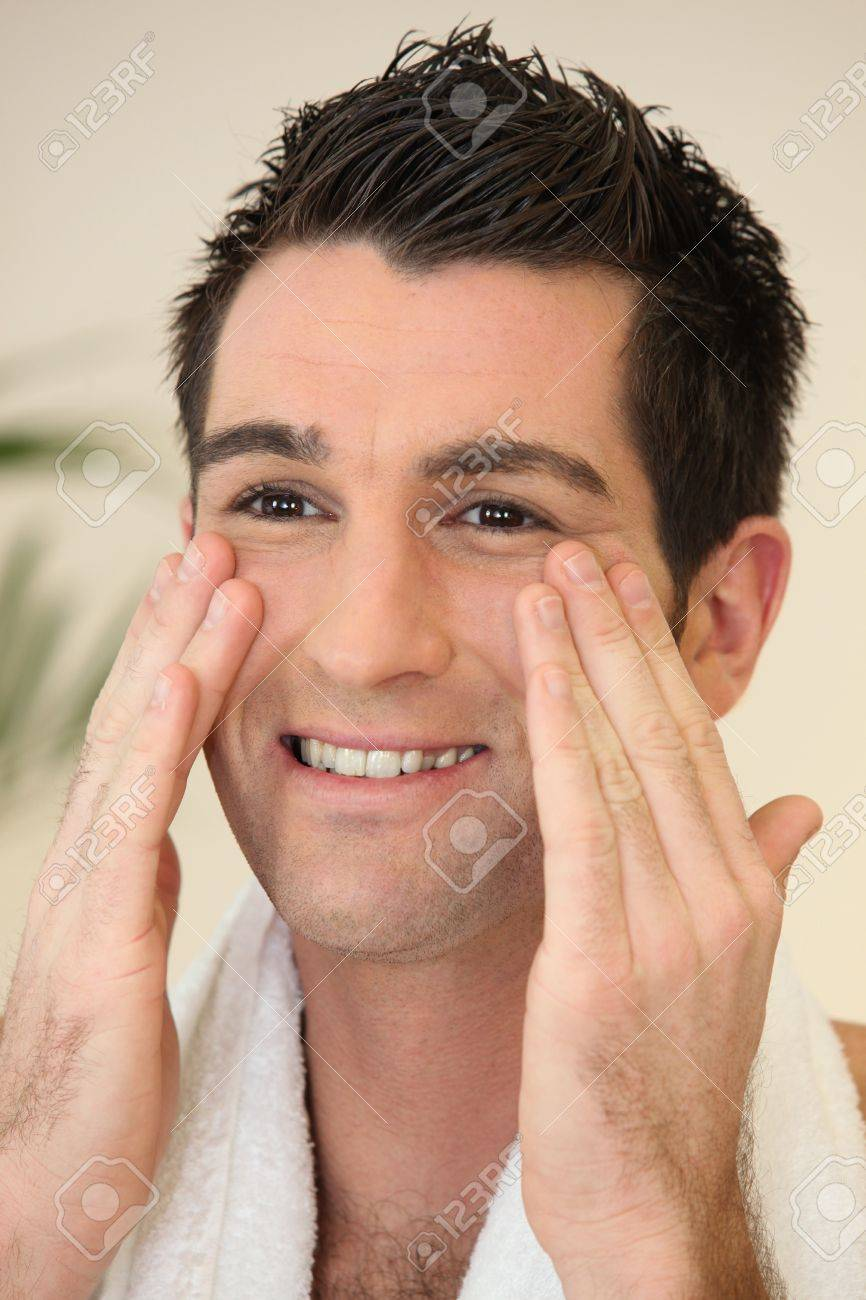 Portrait of a smiling man applying cream Stock Photo - 11132473