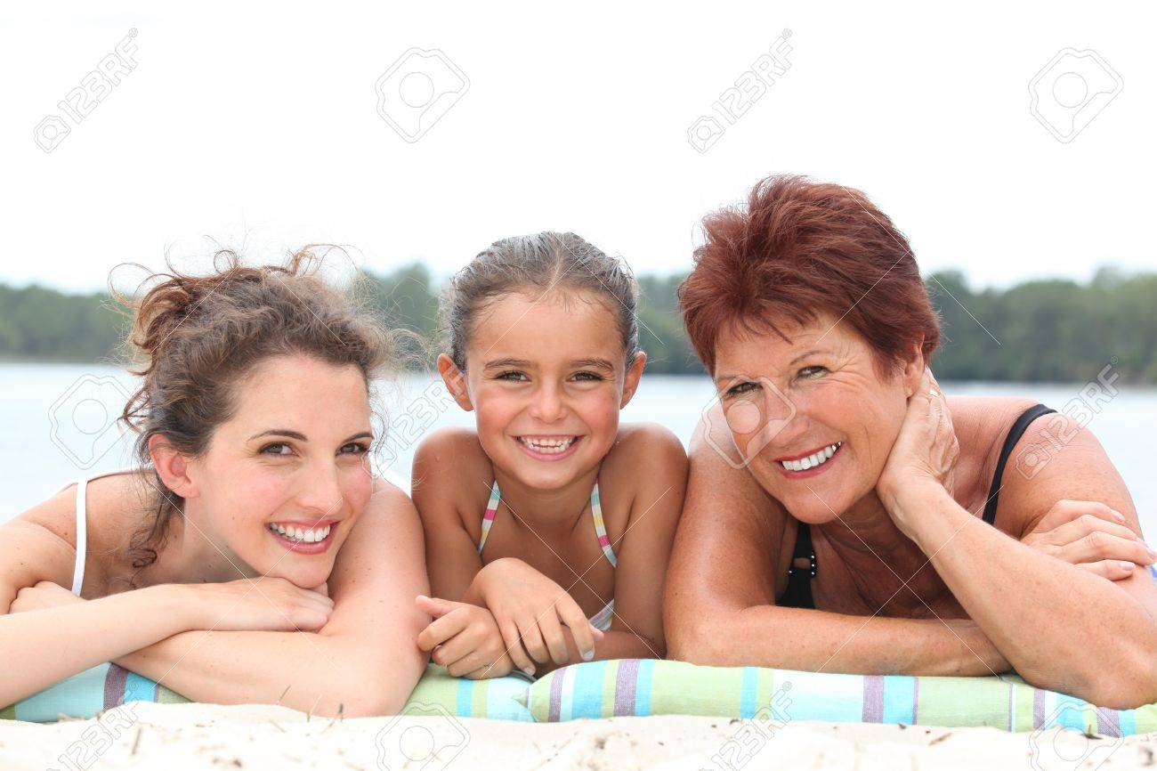 a 30 years old woman, a little girl and a 55 years old woman lying down on the beach, behind sea and forest background Stock Photo - 11136775