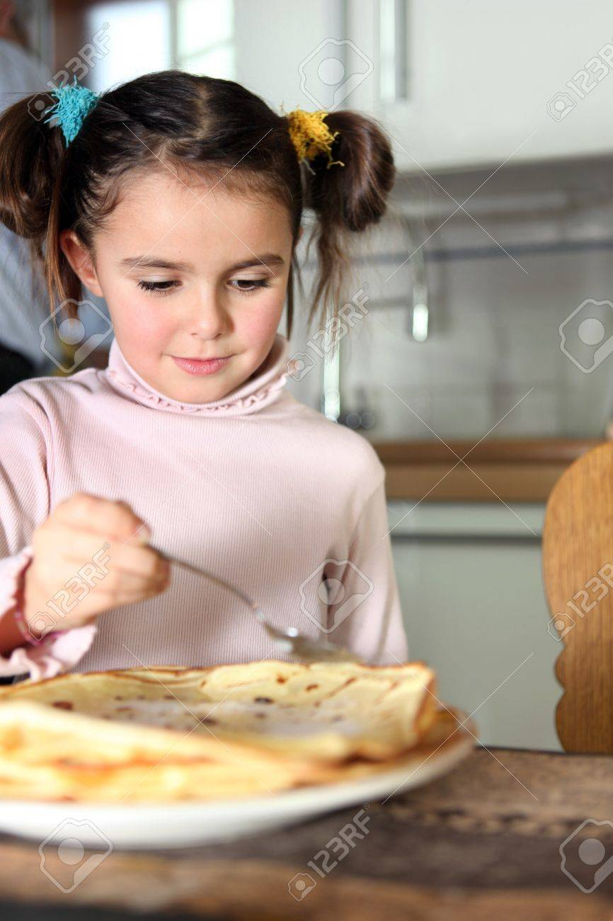 Little girl eating pancakes in kitchen Stock Photo - 11136082