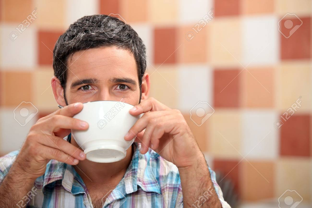 Man drinking from a white bowl in a tiled kitchen Stock Photo - 11135929