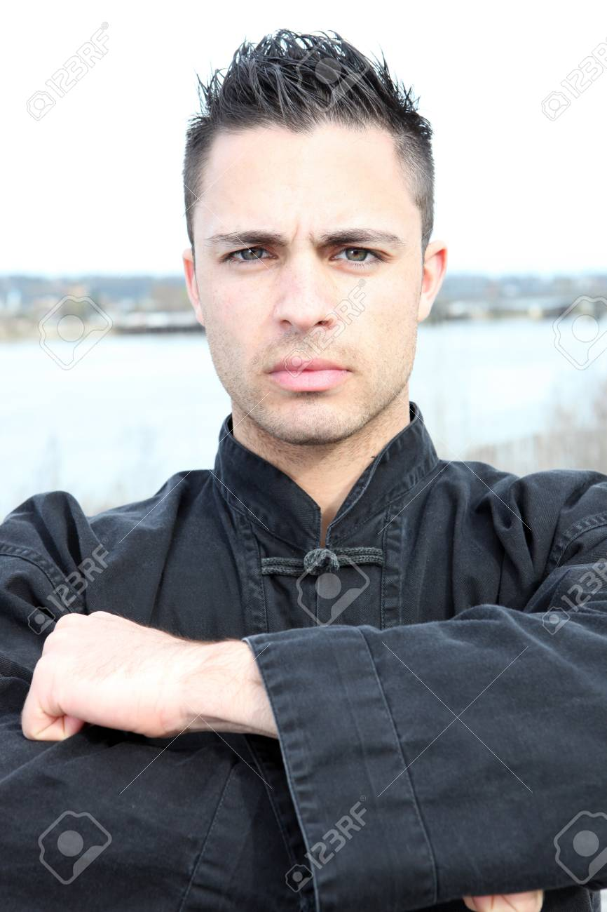 Man dressed in a black martial arts jacket standing by a river Stock Photo - 11135101