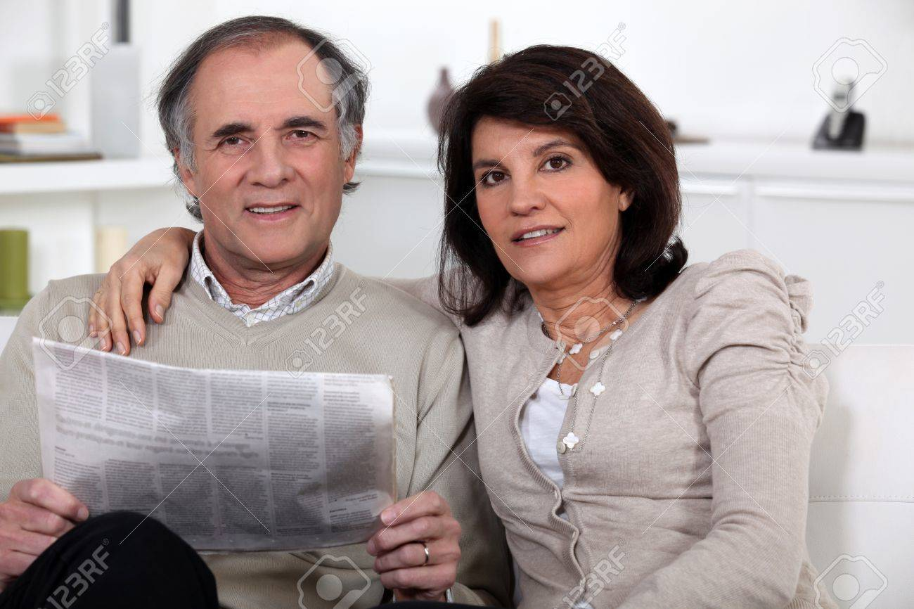 Mature couple sitting reading a newspaper on the sofa Stock Photo - 11306685