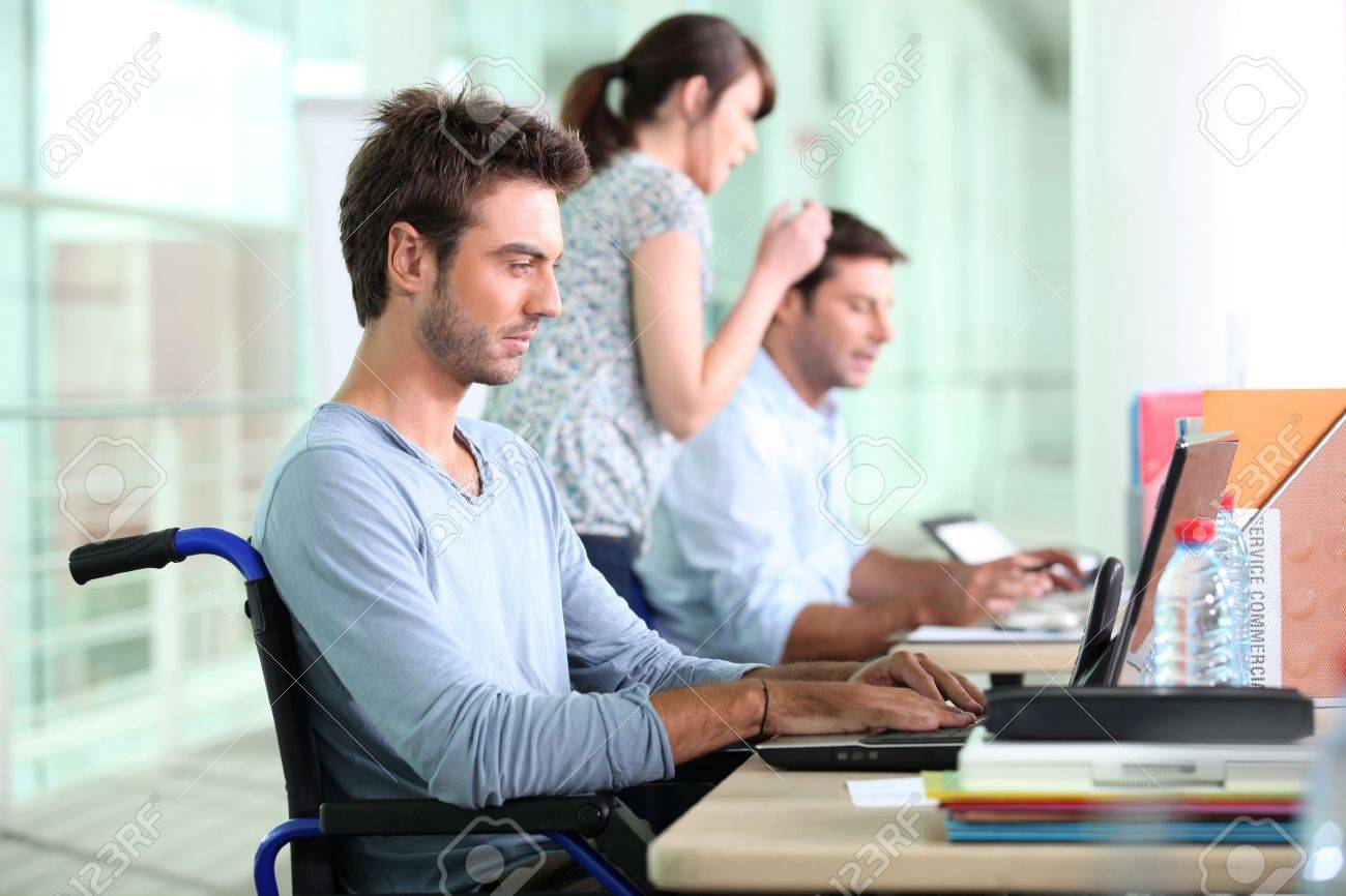 Three people working in a sales department, one of them in a wheelchair. Stock Photo - 11315757