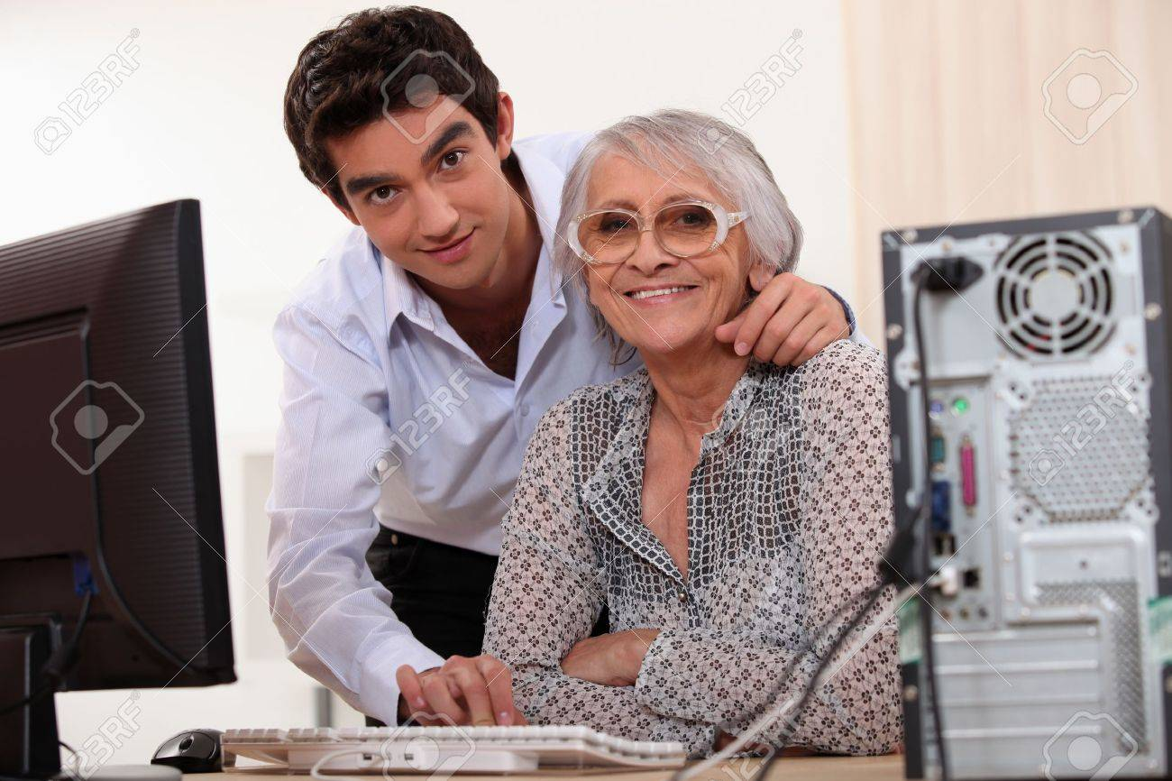 Young man helping an elderly lady use a computer Stock Photo - 11315434