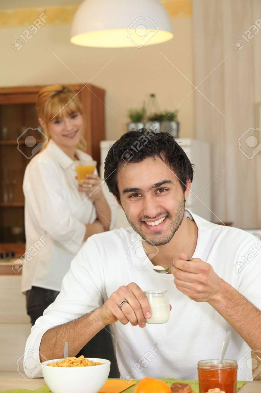 Happy man eating yoghurt for breakfast Stock Photo - 11389431
