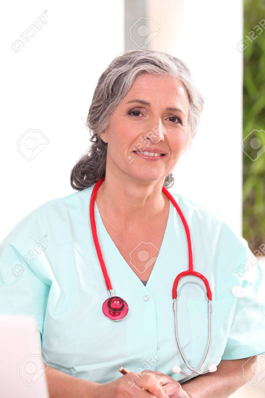 Medic in scrubs working at a desk Stock Photo - 11457051