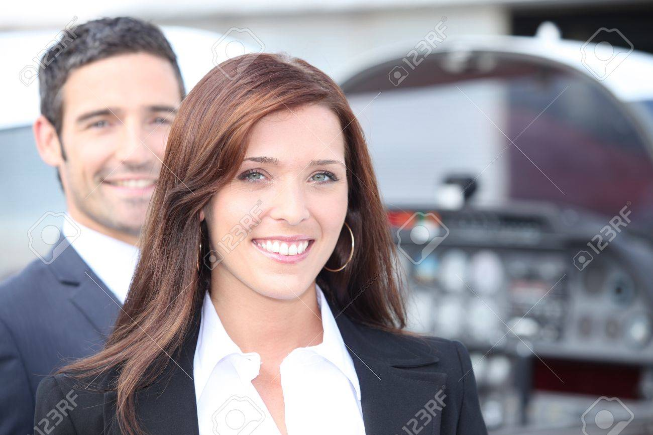 Couple standing by the cockpit of a light aircraft Stock Photo - 11456048