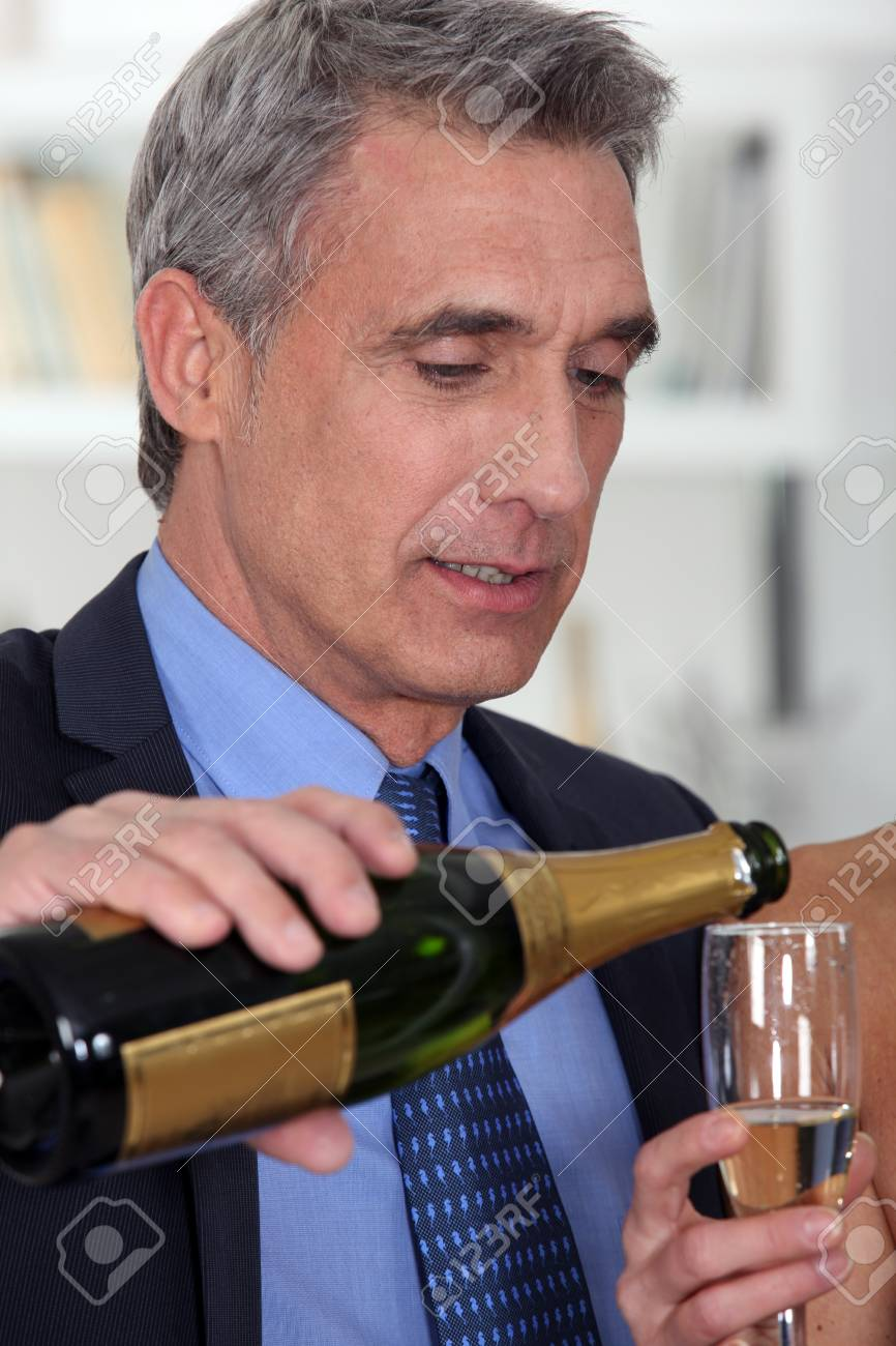 A mature man pouring champagne. Stock Photo - 11756788
