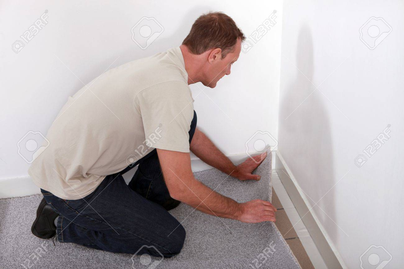 man installing carpet in room stock photo
