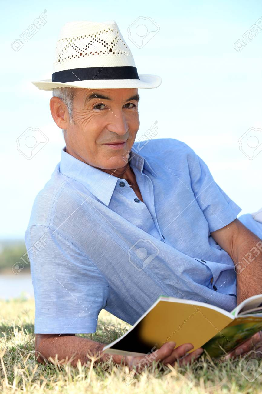 Man in hat reading in the park Stock Photo - 11776934