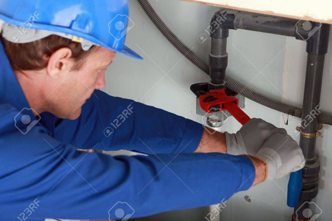 Man using a large red wrench on some interior water pipes Stock Photo - 11797486
