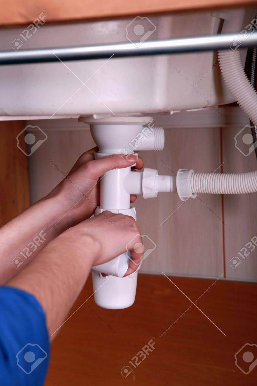 plumber fitting the waste pipe to a kitchen sink stock photo 11834003 - Kitchen Sink Waste Fittings