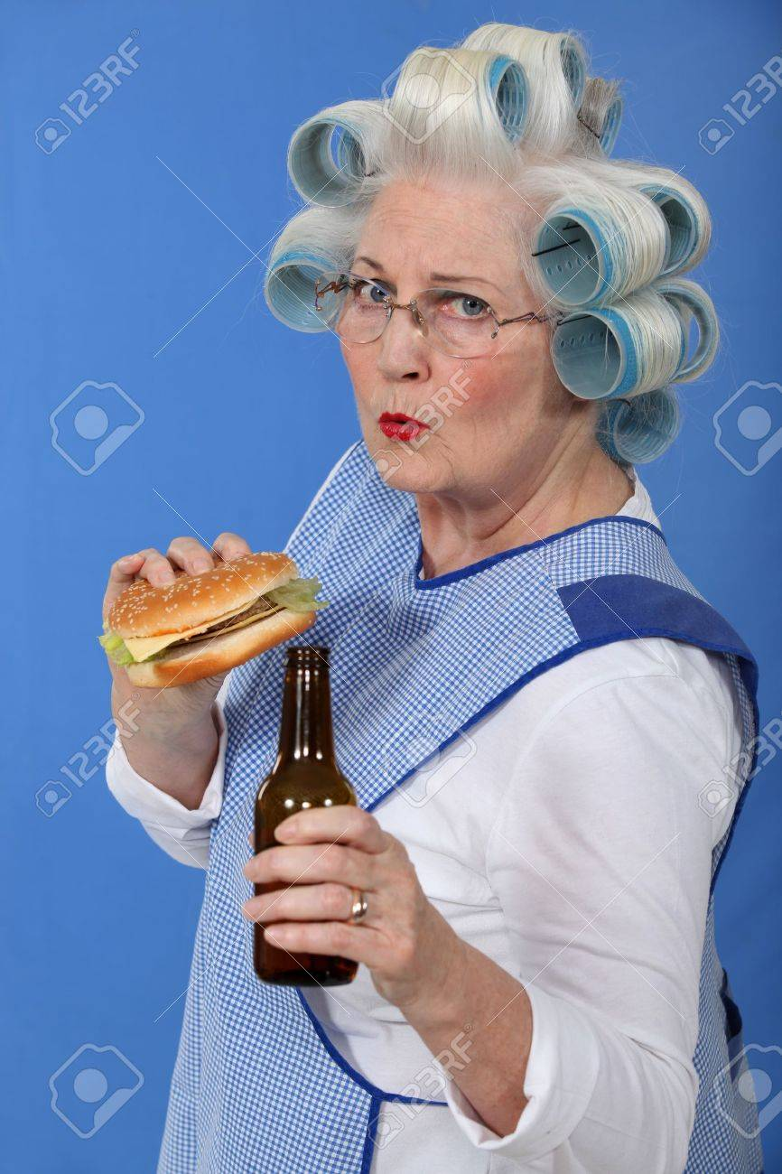 funny picture of grandma with hair curlers relishing cheeseburger with beer Stock Photo - 11842594