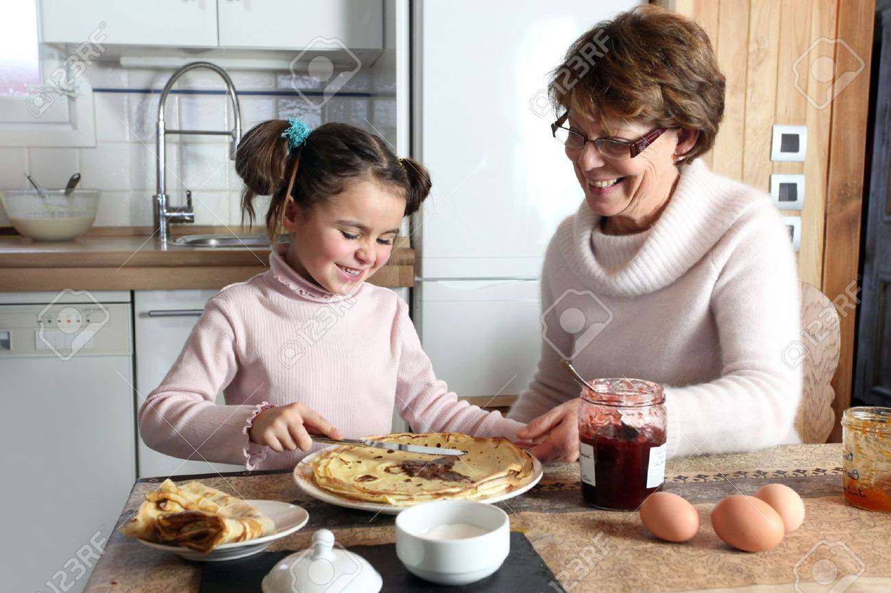 Young girl preparing crepes with her grandmother Stock Photo - 11843810