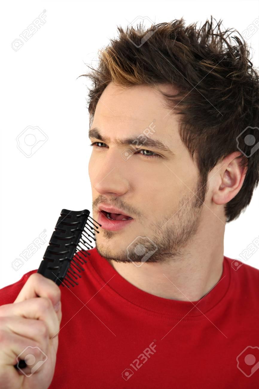 El hombre joven con cepillo de pelo como micrófono improvisado Foto de  archivo - 11913491 716b8e69338d