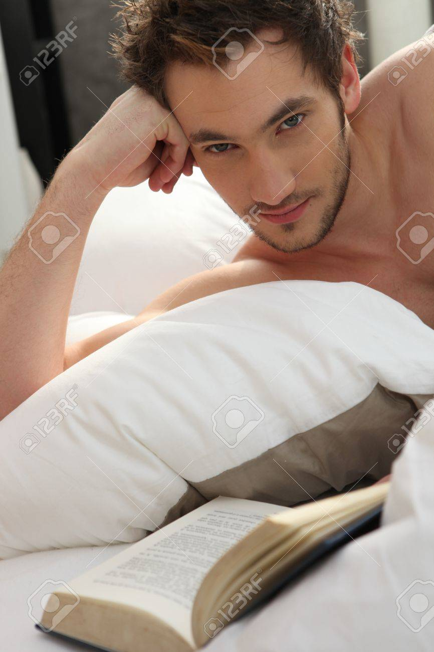 Young man reading a book in bed Stock Photo - 11913577