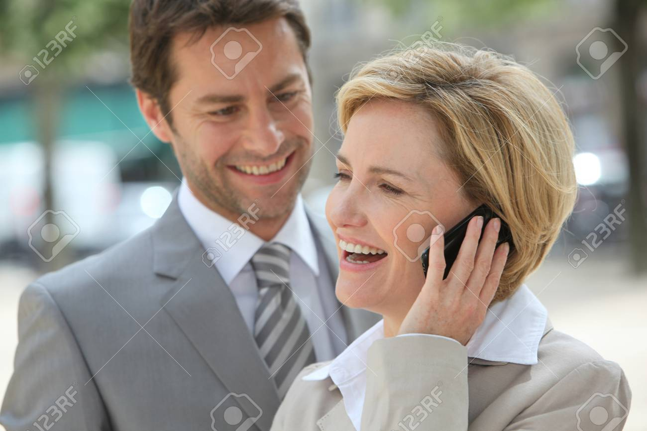 Businessman and woman laughing on the phone. Stock Photo - 11935000