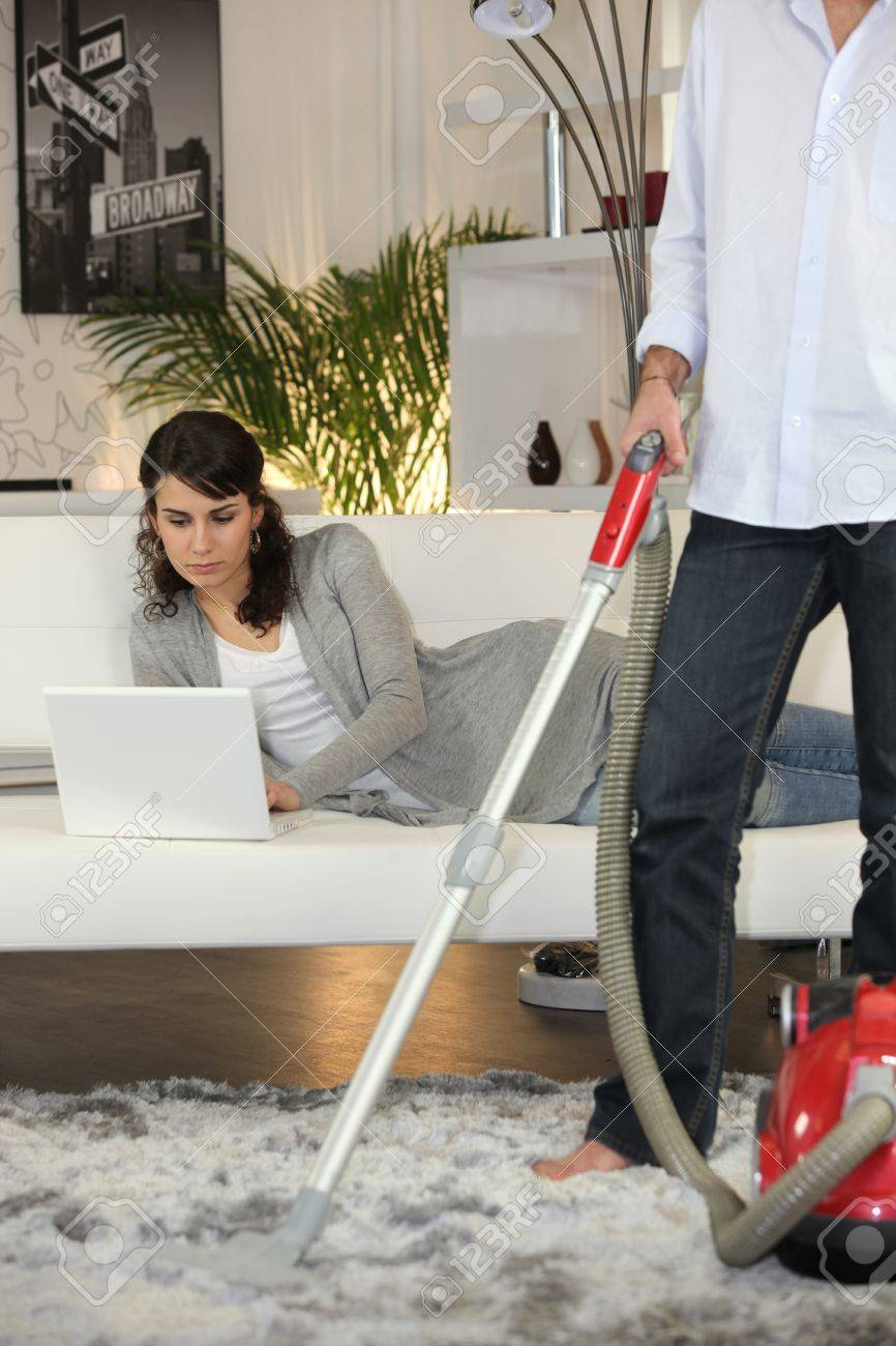 Man vacuuming and woman laid with laptop Stock Photo - 11947294