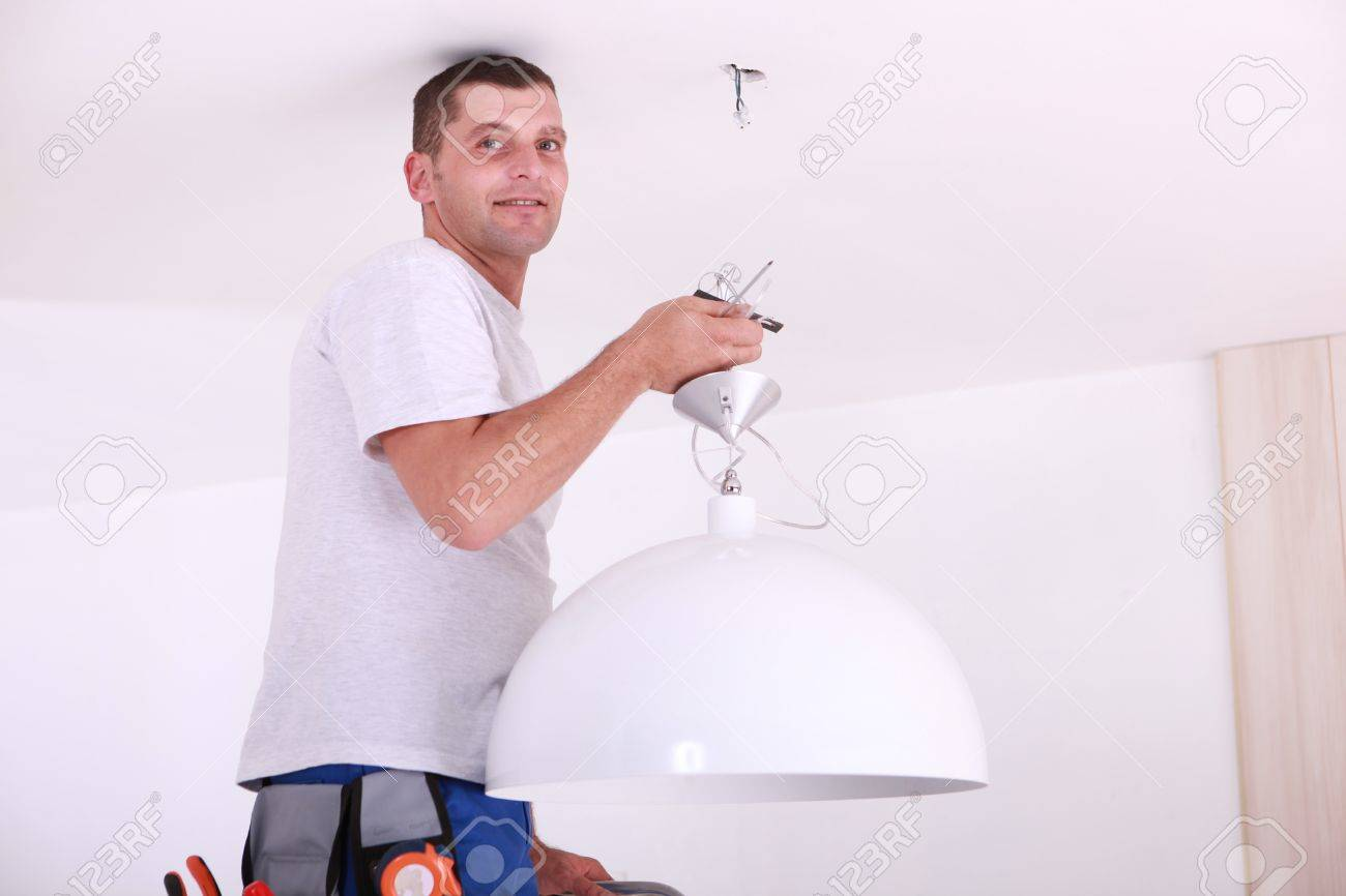 Man installing a ceiling light Stock Photo - 11971514