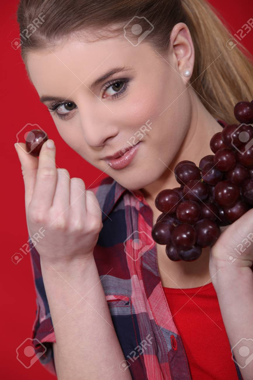 Attractive woman eating grapes Stock Photo - 11972631
