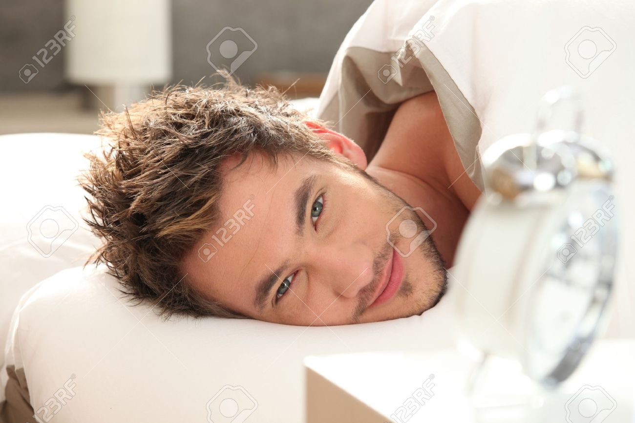 young man in bed waking up Stock Photo - 12103714