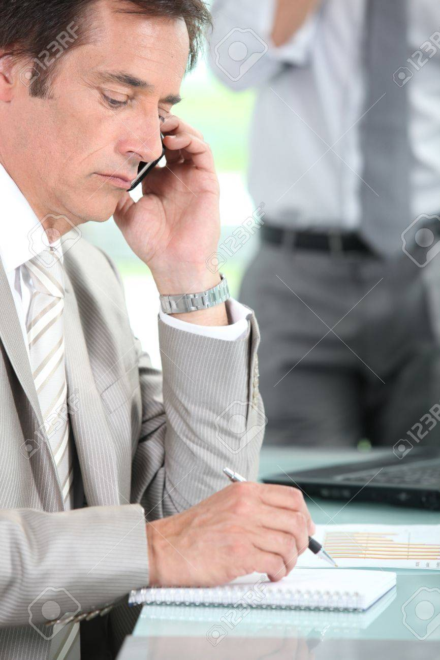 A businessman phoning and taking notes in his office. Stock Photo - 12019579